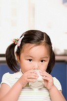 Portrait of a girl drinking milk from a glass
