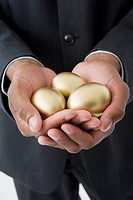 Mixed race businessman holding three golden eggs
