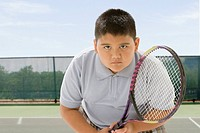 Hispanic boy playing tennis