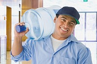 Hispanic delivery man carrying large water bottle