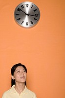 Close_up of a female office worker with a clock above her head