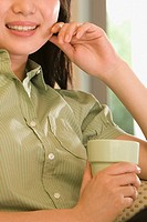 Close_up of a young woman holding a coffee cup and smiling