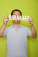 Male office worker holding a scissors and a paper chain