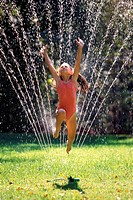 Girl in swimsuit jumping through lawn sprinkler in a garden