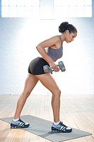 Muscular young woman is exercising with weights in gym.