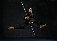 Young man performing martial arts with stick
