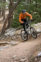Man riding mountain bike on trail in forest