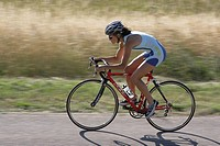 Female cyclist on road in countryside