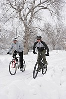 Two men riding mountain bikes in snow