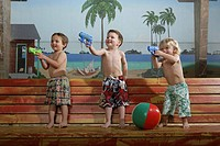 Three boys 4_5 playing with water guns on bench