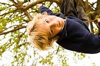 Portrait of boy 10_11 hanging from tree