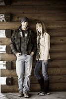 Young couple standing outside log cabin