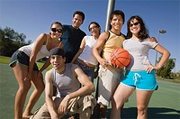 Group of young adults at basketball court.