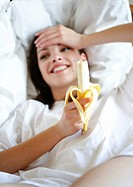 young woman eating a banana on the bed