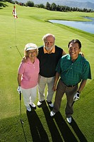Senior couple with instructor on golf course smiling portrait elevated view