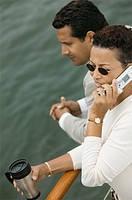 Couple relaxing on yacht woman talking on mobile phone elevated view