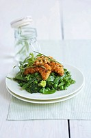 Crispy chicken pieces on green vegetables