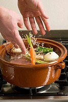 Adding vegetables to meat in pot_au_feu pot