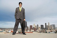 Business man standing on city rooftop