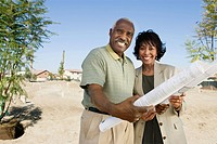 Middle_aged couple holding blueprints in vacant lot portrait