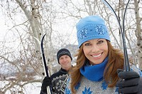 Couple standing outdoors holding skis in snow