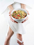 Person in bathrobe holding small bowl of quinoa salad