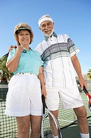 Smiling Couple standing side by side on Tennis Court holding rackets