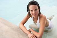 Young woman relaxing in swimming pool portrait elevated view