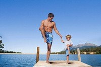 Father and son balancing in lake dock