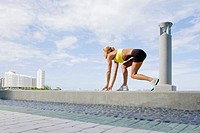 Side profile of a mid adult woman in a running position on the ledge