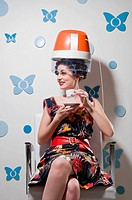 Young woman sitting under a hair dryer and drinking tea