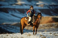 A cowgirl out for a ride in the snowy mountains of Shell, Wyoming, USA