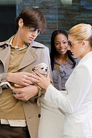 Young man and a young woman looking at a puppy