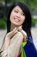 Close_up of a young woman carrying shopping bags and smiling