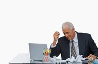 Businessman sitting at a desk with crumpled paper on the desk