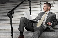 Businessman sitting on a staircase and using a laptop