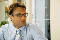 Close_up of a businessman wearing eyeglasses and thinking