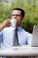 Close_up of a businessman sitting in front of a laptop and drinking coffee