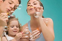 Mid adult couple blowing bubbles with their daughter (thumbnail)