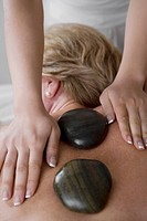 Rear view of a mature woman receiving a back massage from a massage therapist
