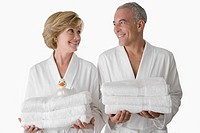 Close_up of a senior man with a mature woman standing together and holding folded towels