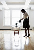 Woman watering bonsai tree in empty room