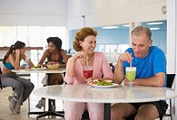 Mature couple eating in health club café