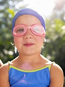 Girl wearing swimming goggles and cap portrait