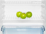 Three green apples in fridge close_up