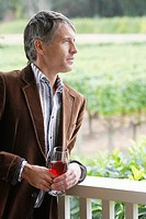 Mid adult man drinking red wine on patio portrait