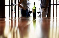 Couple standing near bottle of red wine focus on foreground