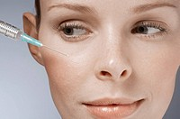 Syringe near woman´s face, close_up