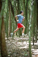 Young man running in forest