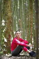 Young woman in sports clothing sitting in forest